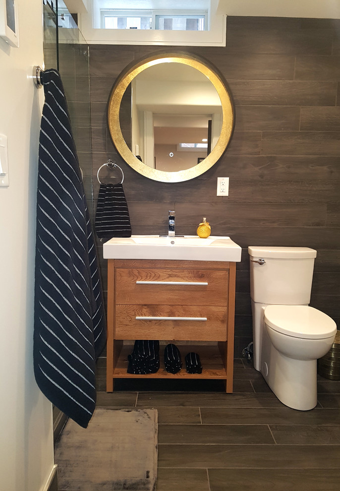 Mid-sized minimalist black tile and ceramic tile porcelain tile and black floor bathroom photo in Toronto with furniture-like cabinets, brown cabinets, a two-piece toilet, white walls, a vessel sink, solid surface countertops and white countertops