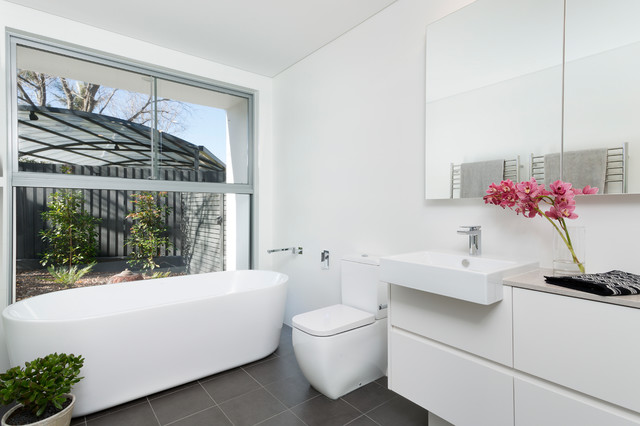 Freestanding bathtub - modern gray tile, white tile and porcelain tile ceramic floor freestanding bathtub idea in Sydney with flat-panel cabinets, white cabinets, a two-piece toilet, white walls and granite countertops