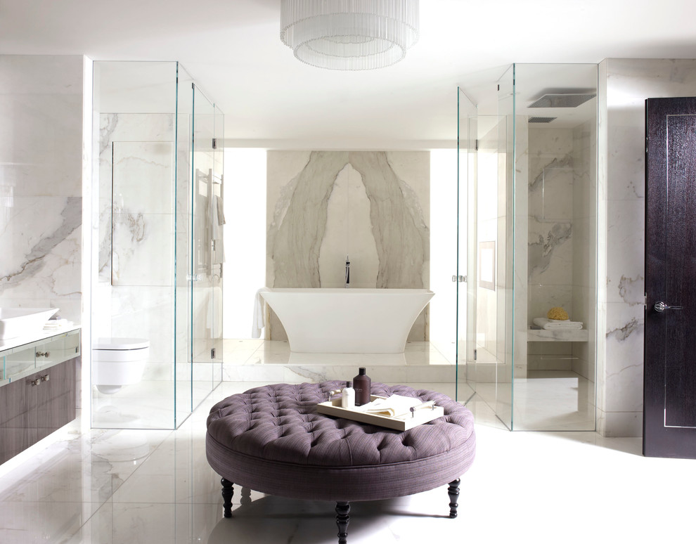 Freestanding bathtub - contemporary white tile and stone slab freestanding bathtub idea in London