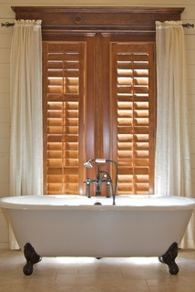 Stained Plantation Shutters Next To Claw Foot Tub