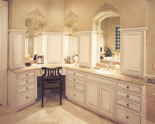 Stencils above each mirror resemble tiaras in this traditionally feminine dressing room, part of a large master bathroom.