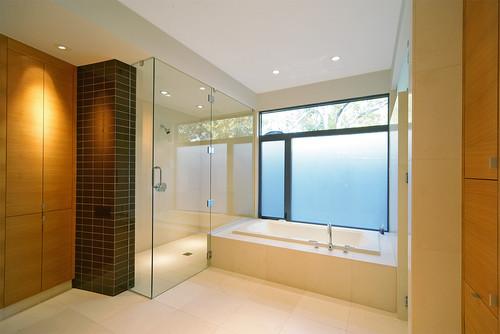 baño simple con ducha y bañera ideal para un apartamento