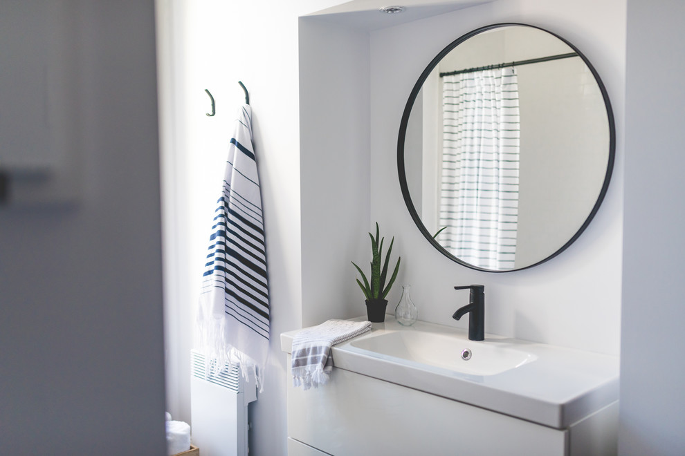 Bathroom - mid-sized scandinavian 3/4 gray tile and porcelain tile ceramic tile bathroom idea in Montreal with flat-panel cabinets, white cabinets, a one-piece toilet, white walls, a wall-mount sink and quartzite countertops