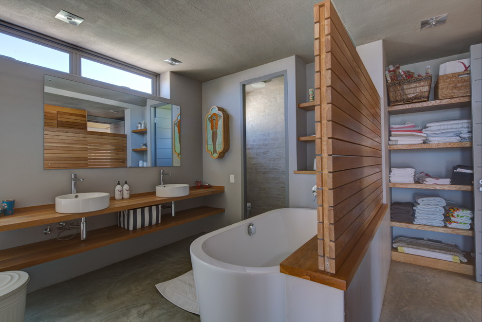 Freestanding bathtub - coastal freestanding bathtub idea in Other with a vessel sink and open cabinets