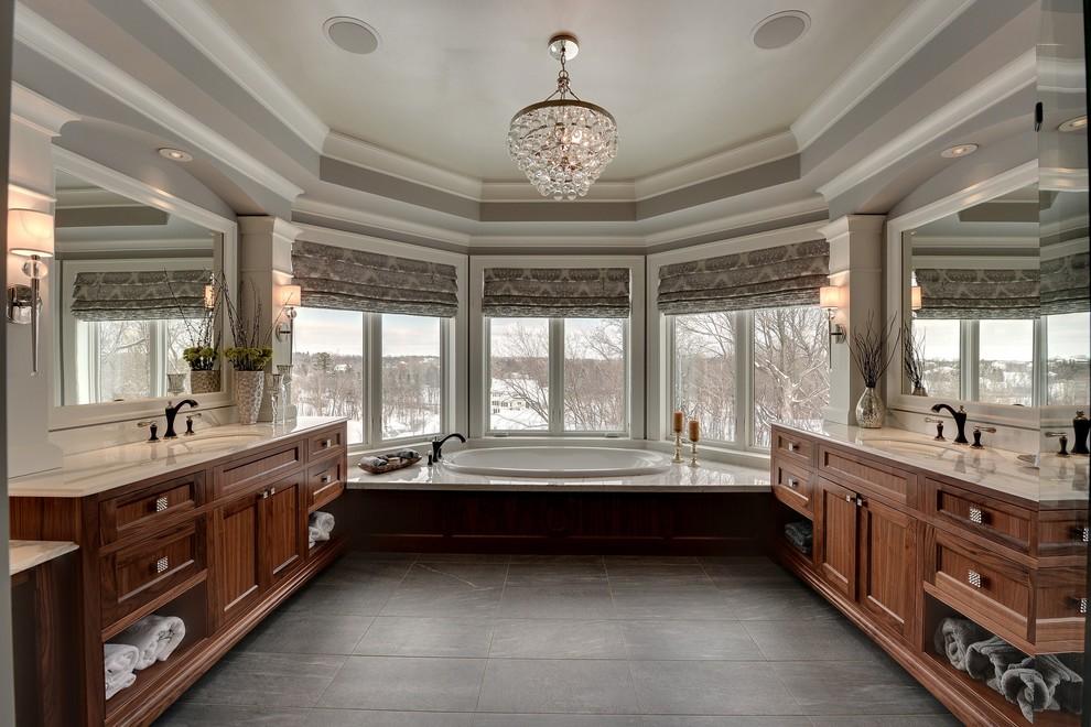 Foto de cuarto de baño clásico con lavabo bajoencimera, puertas de armario de madera en tonos medios, baldosas y/o azulejos negros y bañera encastrada