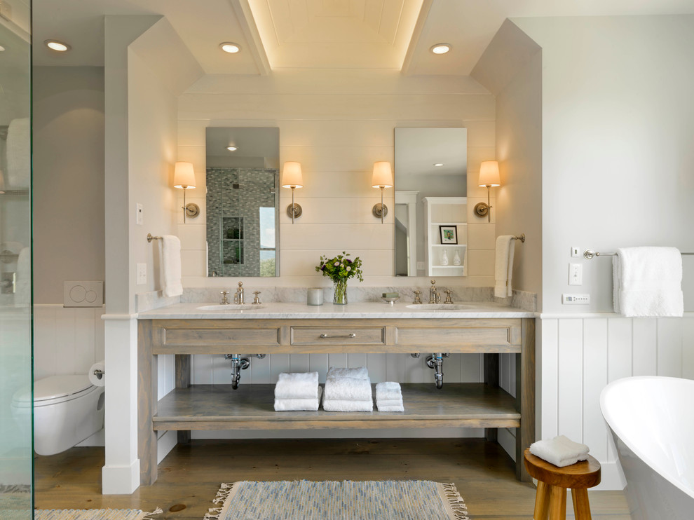 Example of a cottage master freestanding bathtub design in Burlington with an undermount sink, open cabinets, distressed cabinets, a wall-mount toilet and white walls