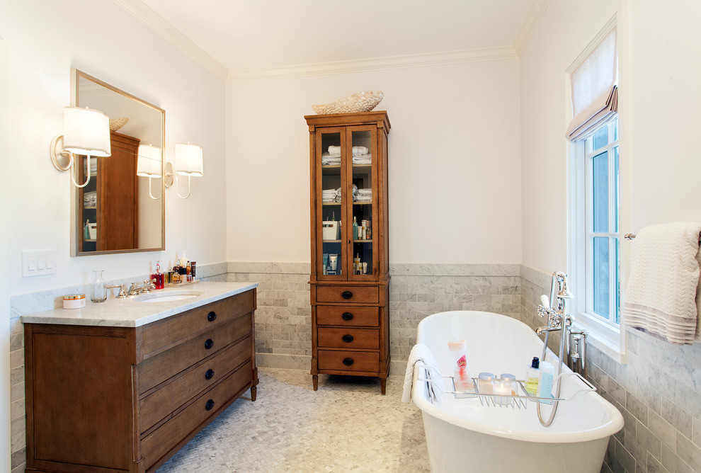 Freestanding bathtub - mid-sized traditional 3/4 gray tile and stone tile mosaic tile floor and gray floor freestanding bathtub idea in Austin with an undermount sink, furniture-like cabinets, dark wood cabinets, white walls and quartzite countertops