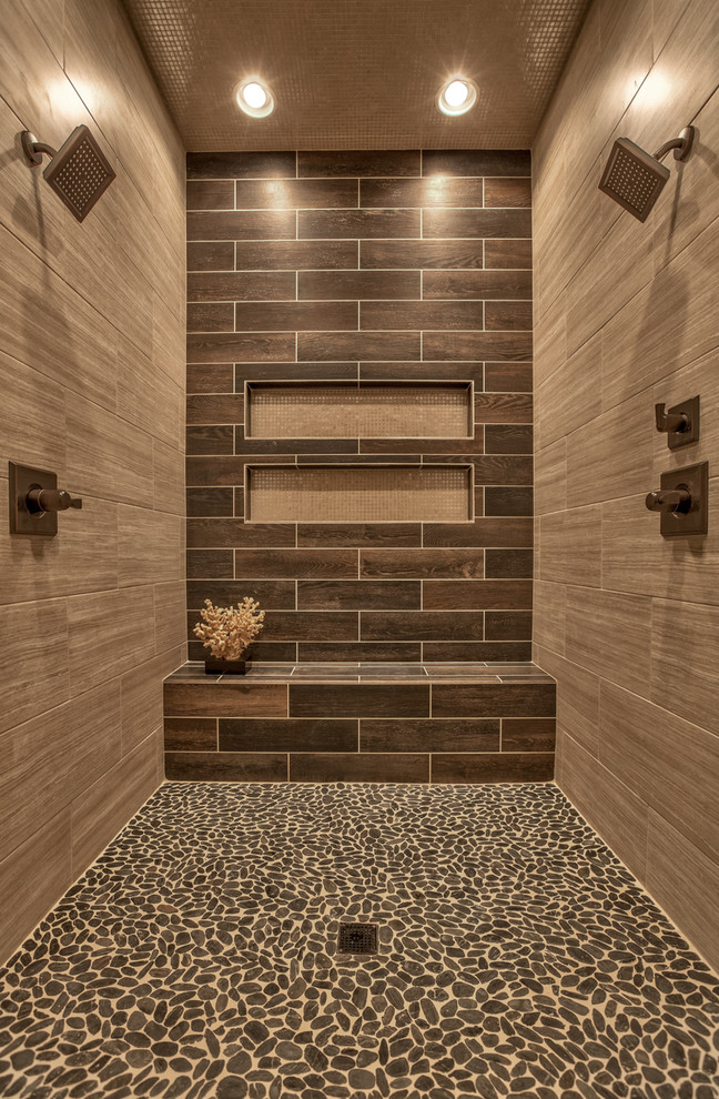 Double shower - transitional brown tile pebble tile floor double shower idea in Omaha with a niche