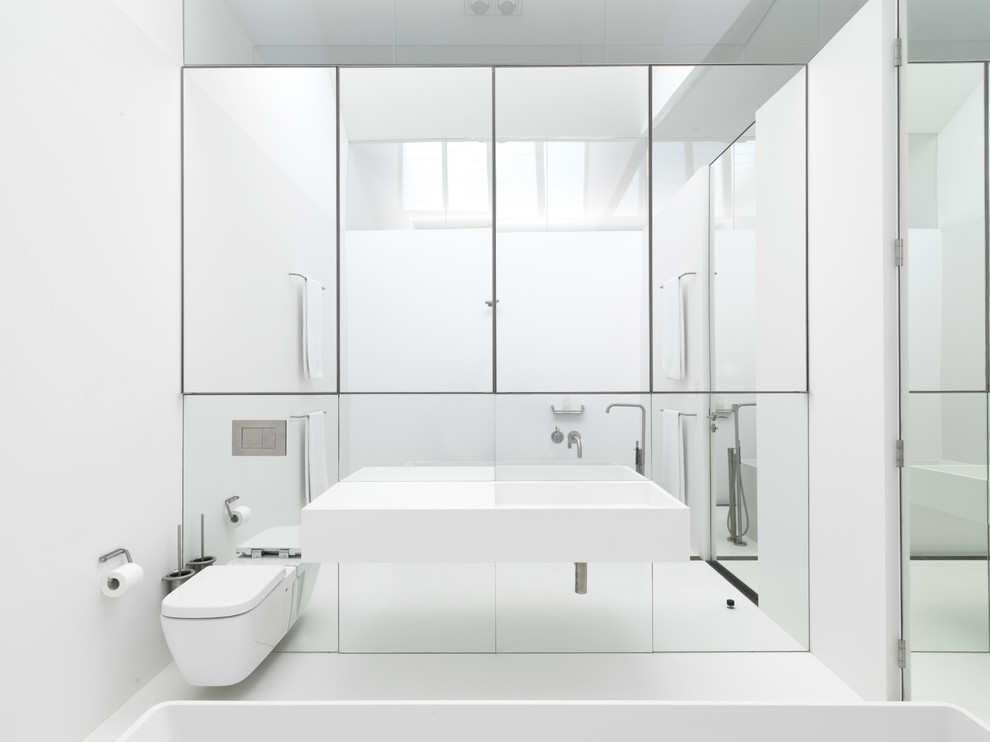 Example of a minimalist freestanding bathtub design in Sydney with a wall-mount sink and a wall-mount toilet