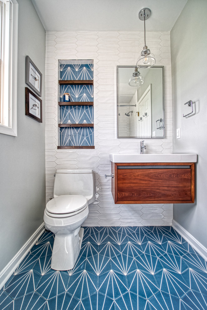 Example of a mid-sized transitional 3/4 white tile and ceramic tile ceramic tile and blue floor bathroom design in Baltimore with flat-panel cabinets, medium tone wood cabinets, a one-piece toilet, gray walls, an integrated sink, solid surface countertops and white countertops