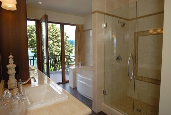 Example of a mid-sized tuscan master ceramic tile ceramic floor and brown floor bathroom design in Vancouver with shaker cabinets, dark wood cabinets, beige walls, a drop-in sink, limestone countertops and a hinged shower door