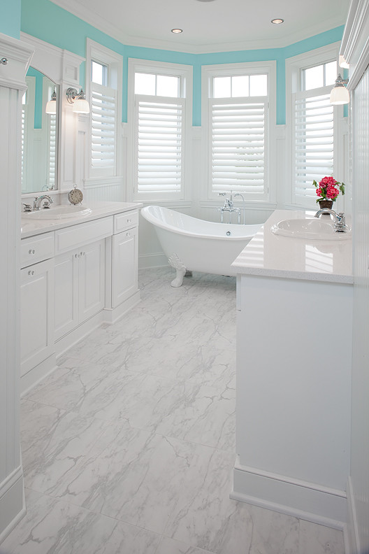Example of a large classic master marble floor freestanding bathtub design in Grand Rapids with raised-panel cabinets, white cabinets, blue walls, a drop-in sink and solid surface countertops