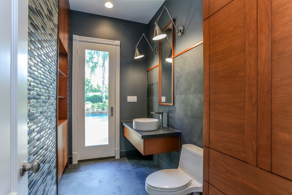 Example of a small trendy 3/4 slate floor and black floor bathroom design in Houston with flat-panel cabinets, medium tone wood cabinets, a one-piece toilet, a vessel sink and gray walls