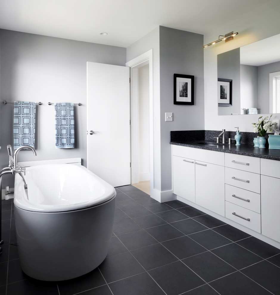 Example of a trendy black floor freestanding bathtub design in Burlington with black countertops