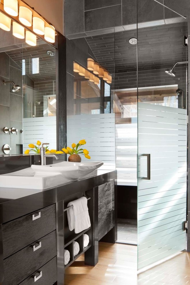 Trendy gray tile and porcelain tile walk-in shower photo in Denver with a vessel sink, furniture-like cabinets, black cabinets and quartzite countertops