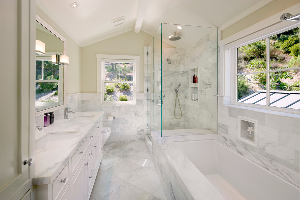 Mid-sized elegant master white tile corner shower photo in Santa Barbara with an undermount sink, white cabinets, an undermount tub, beige walls and a niche
