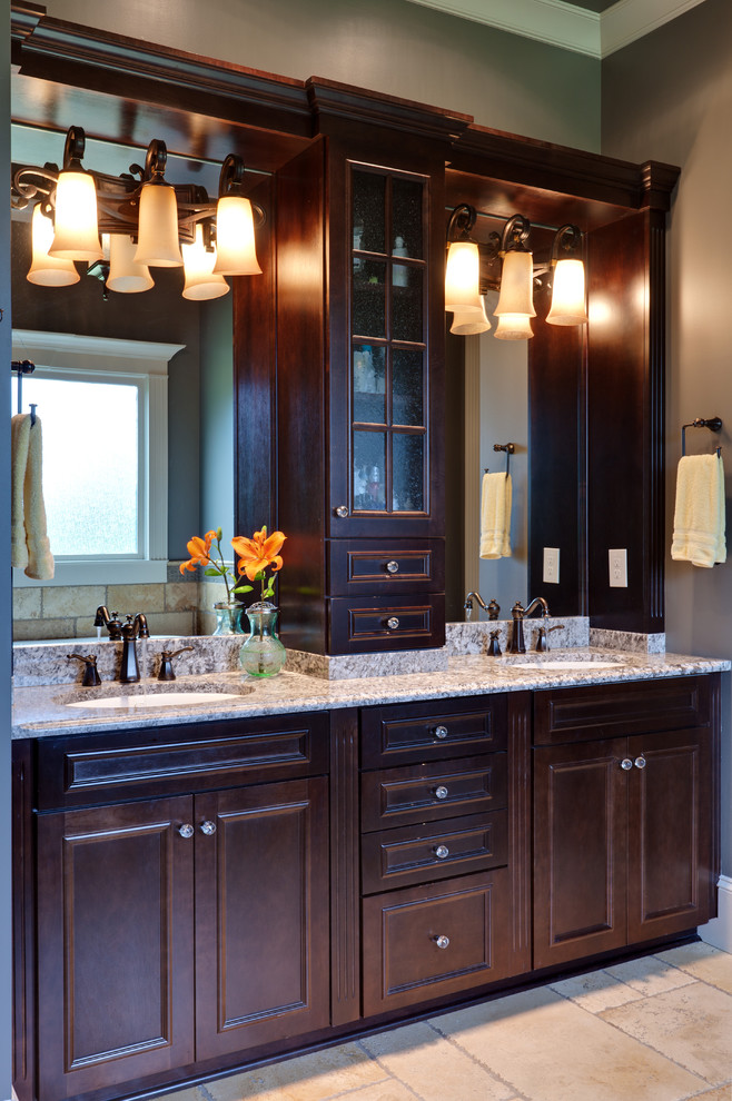 Inspiration for a timeless beige tile bathroom remodel in Atlanta with an undermount sink, recessed-panel cabinets and dark wood cabinets