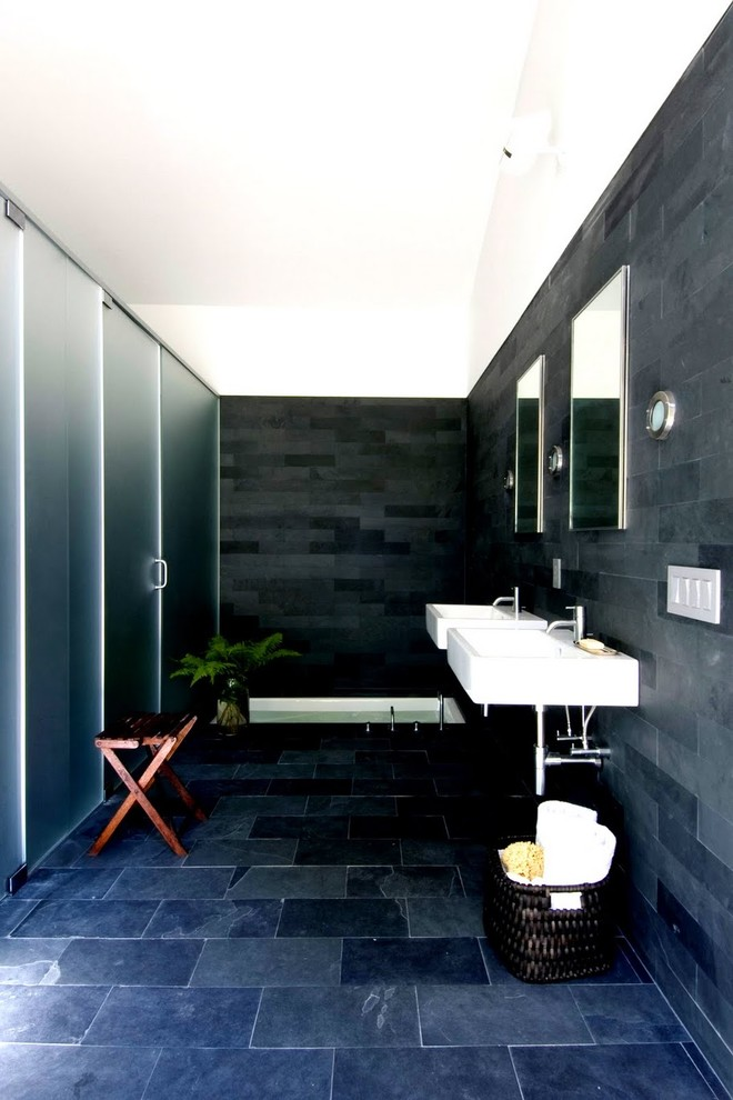 Trendy slate tile slate floor bathroom photo in New York with a wall-mount sink and black walls