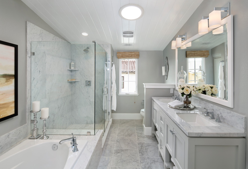 Example of a classic master gray tile drop-in bathtub design in San Francisco with recessed-panel cabinets, gray cabinets, gray walls, an undermount sink and a hinged shower door