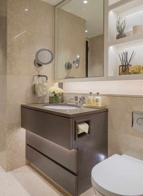 Example of a trendy beige tile bathroom design in London with flat-panel cabinets, brown cabinets, a one-piece toilet and an undermount sink