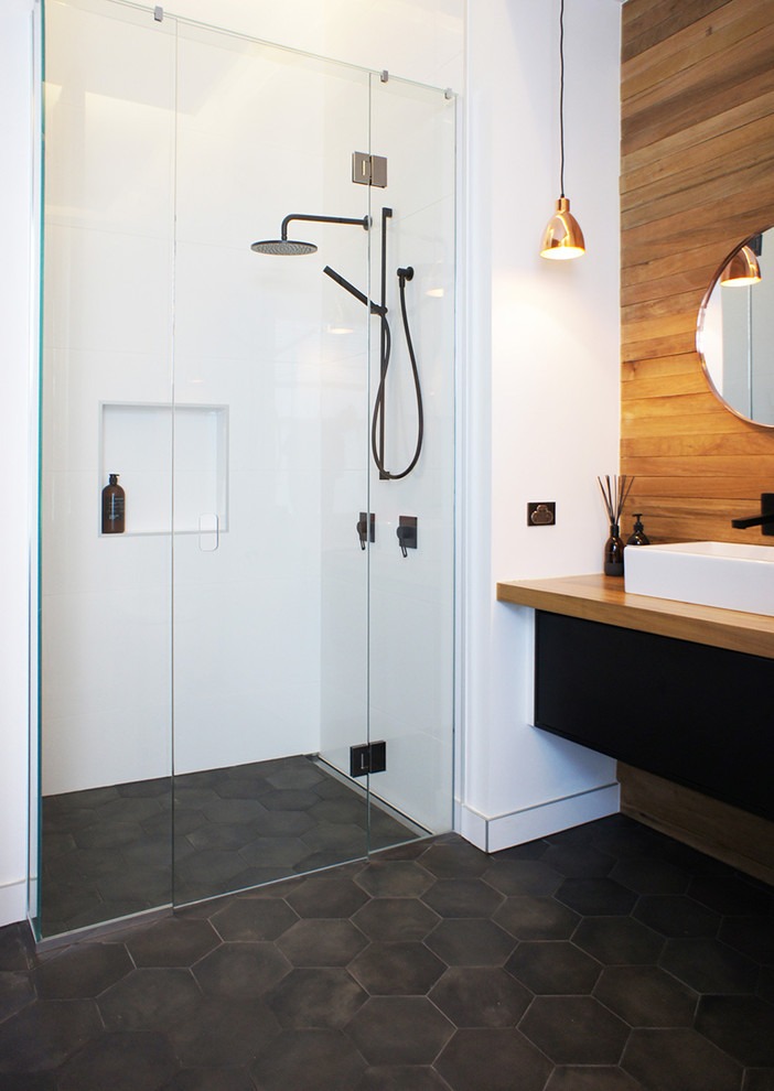 Alcove shower - scandinavian 3/4 porcelain tile and white tile black floor alcove shower idea in Auckland with a vessel sink, wood countertops and brown countertops