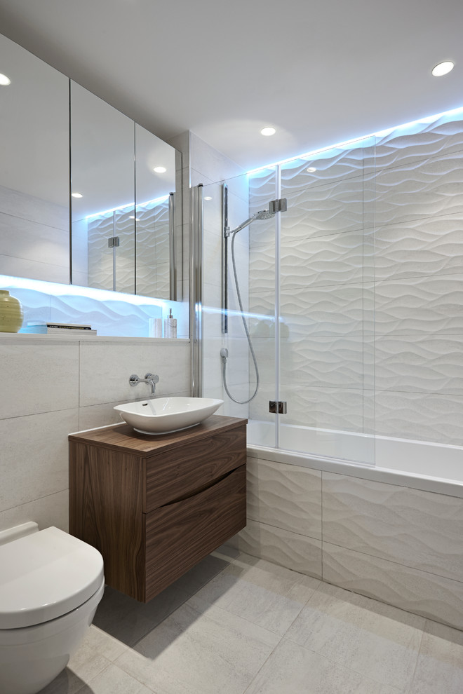 Trendy white tile bathroom photo in London with a vessel sink, flat-panel cabinets, dark wood cabinets, wood countertops, a wall-mount toilet and brown countertops