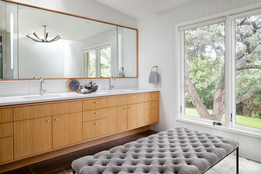 Example of a large trendy master white tile and mosaic tile limestone floor bathroom design in Austin with an undermount sink, flat-panel cabinets, medium tone wood cabinets and solid surface countertops