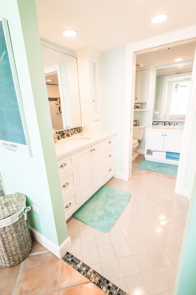 Inspiration for a mid-sized coastal 3/4 beige tile, black and white tile, brown tile and mosaic tile alcove shower remodel in Miami with recessed-panel cabinets, white cabinets, a two-piece toilet, green walls, an undermount sink and granite countertops