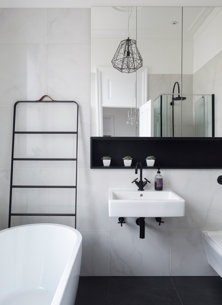 Example of a mid-sized trendy marble tile freestanding bathtub design in London with gray walls and a wall-mount sink