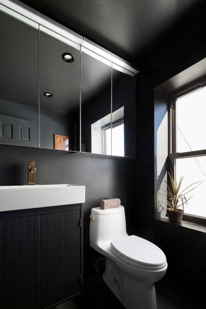 Danish black floor bathroom photo in New York with black cabinets, black walls and a console sink