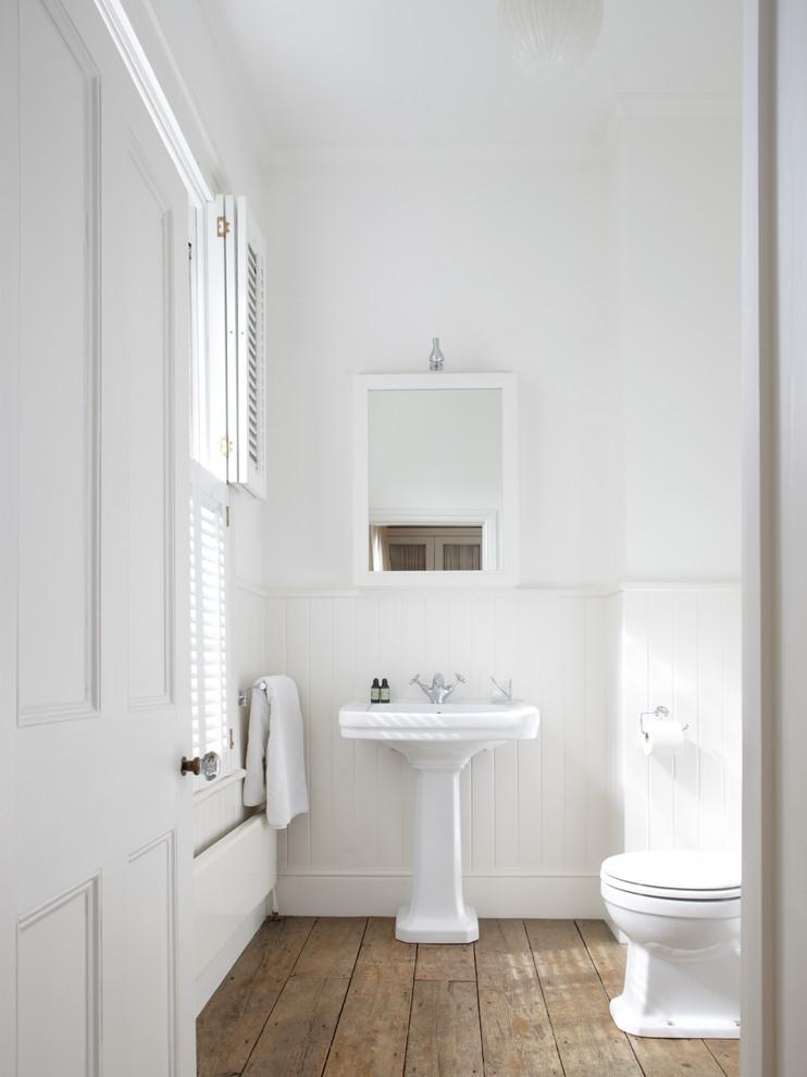Idéer för ett klassiskt badrum, med ett piedestal handfat, vita väggar, mellanmörkt trägolv och brunt golv