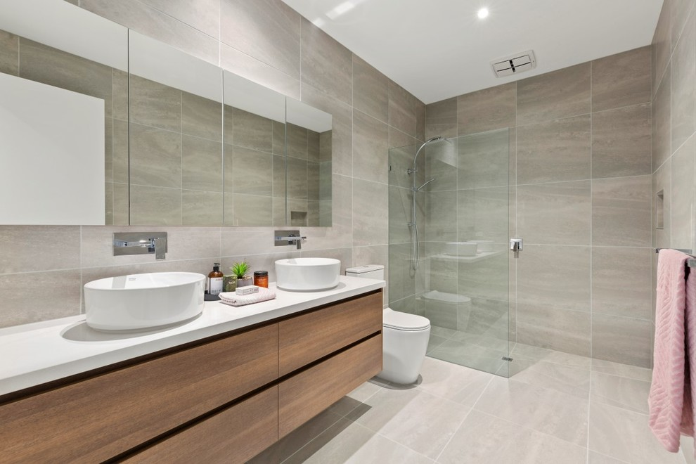 This is an example of a modern 3/4 wet room bathroom in Melbourne with flat-panel cabinets, medium wood cabinets, beige tile, beige walls, a vessel sink, beige floor, an open shower and white benchtops.