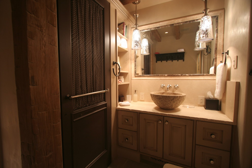 Mid-sized elegant 3/4 beige tile bathroom photo in Denver with raised-panel cabinets, beige walls, a vessel sink, distressed cabinets and soapstone countertops