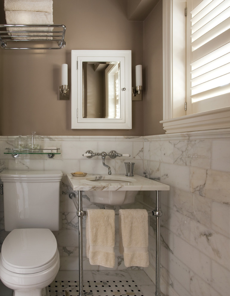 Example of a classic marble tile bathroom design in Boston with a console sink