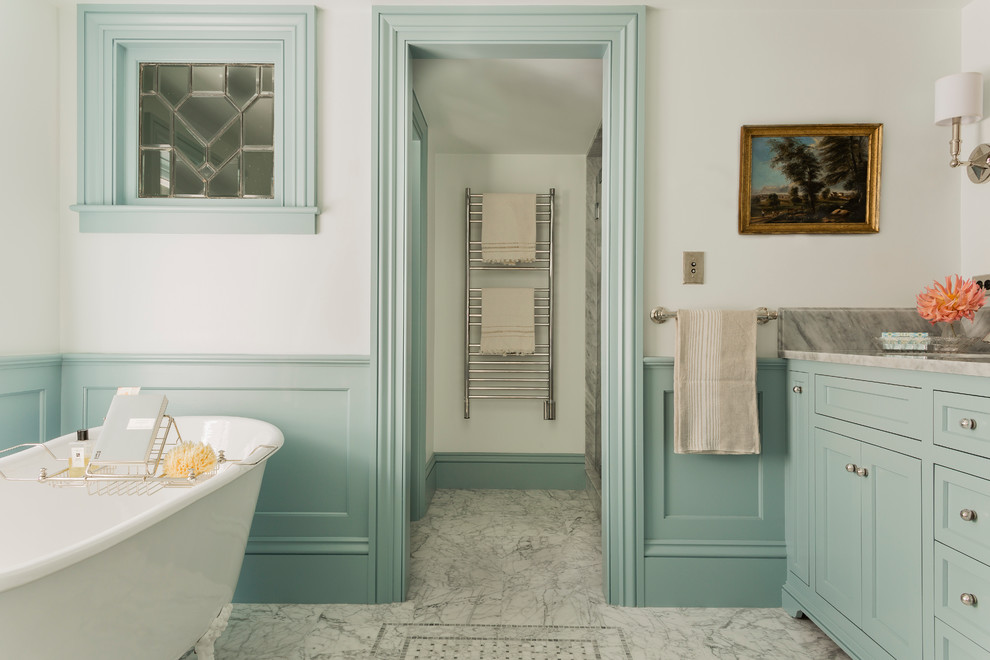 Elegant gray tile claw-foot bathtub photo in Boston with recessed-panel cabinets, blue cabinets and white walls