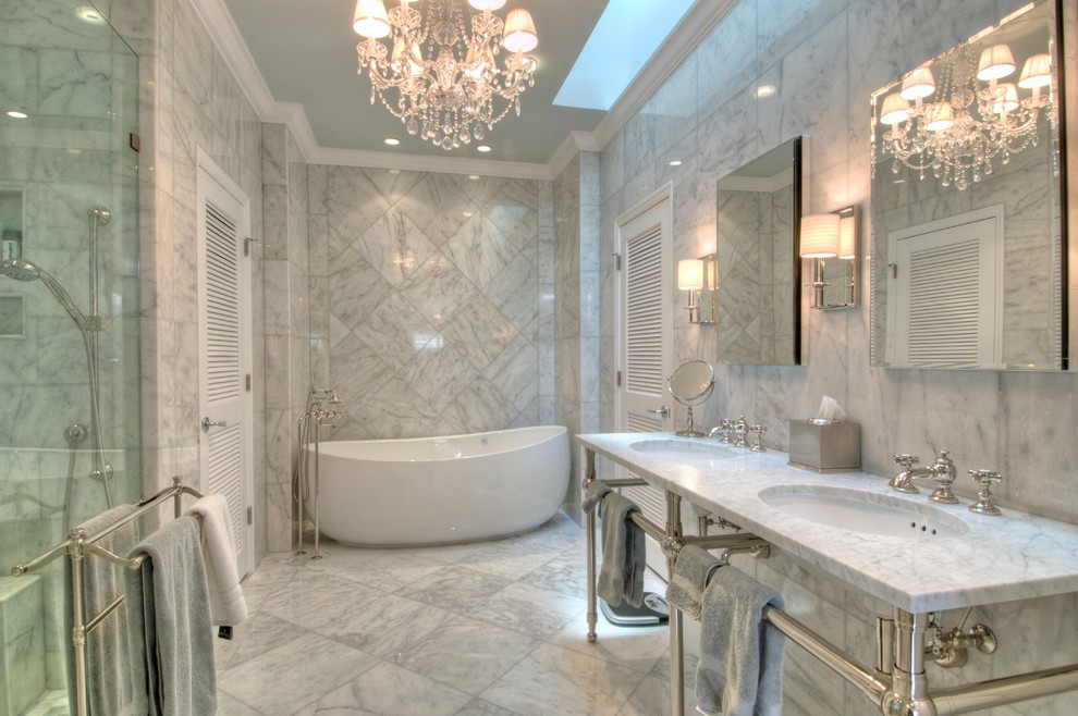 Elegant marble tile freestanding bathtub photo in Tampa with a console sink and marble countertops