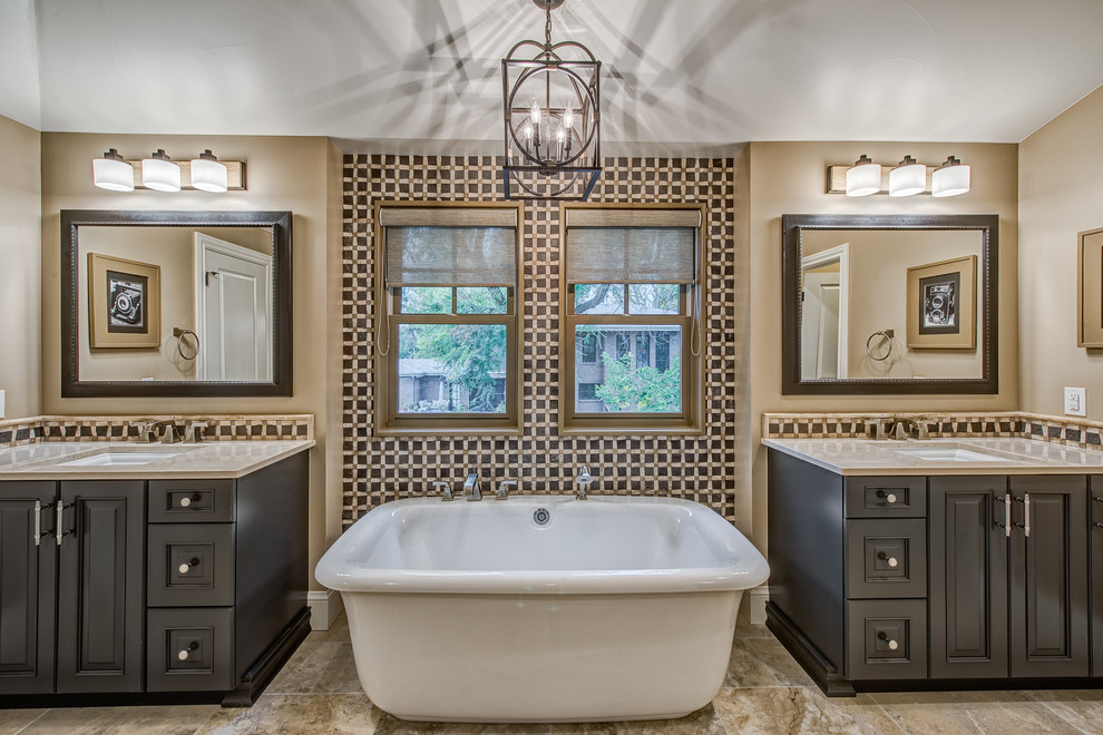 Freestanding bathtub - traditional ceramic tile porcelain tile freestanding bathtub idea in Denver with raised-panel cabinets, beige walls, an undermount sink and dark wood cabinets