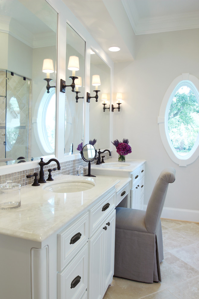 Elegant beige tile and mosaic tile bathroom photo in Houston with an undermount sink, white cabinets and white countertops
