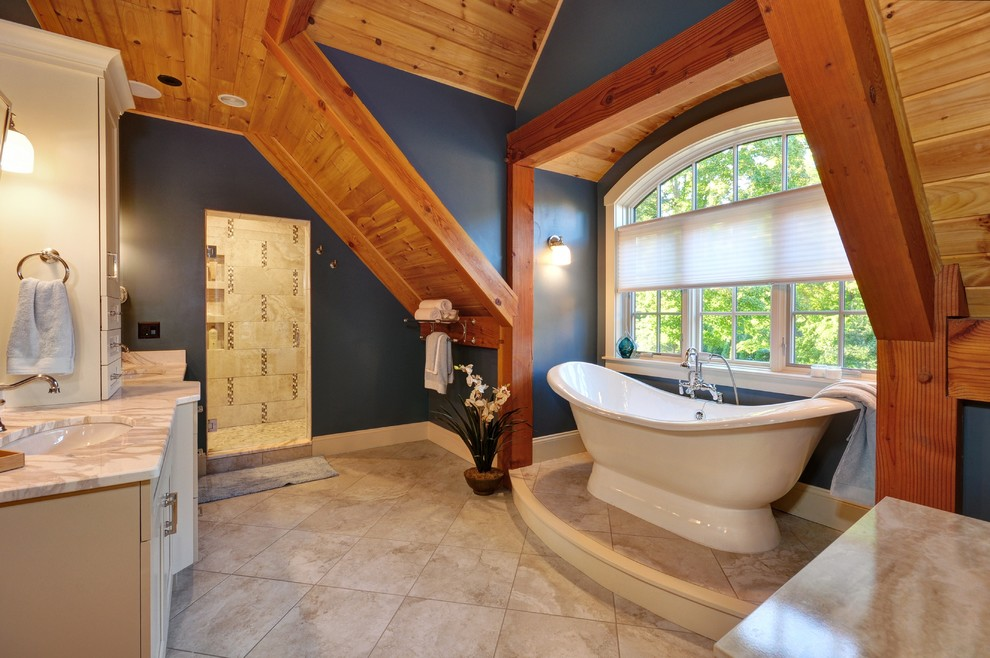 Example of a classic beige tile and gray tile beige floor freestanding bathtub design in Boston with white cabinets, blue walls and an undermount sink