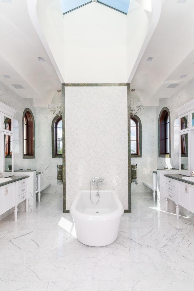 Elegant master white tile freestanding bathtub photo in Miami with white cabinets