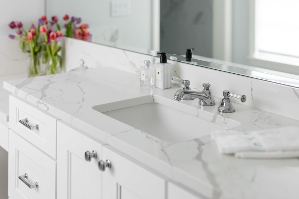 The master vanity of Engineered Quartz is elegant and durable, large enough to display personal items and still drops down to a seated vanity. The Newport Brass chrome faucet is classic and clean, com