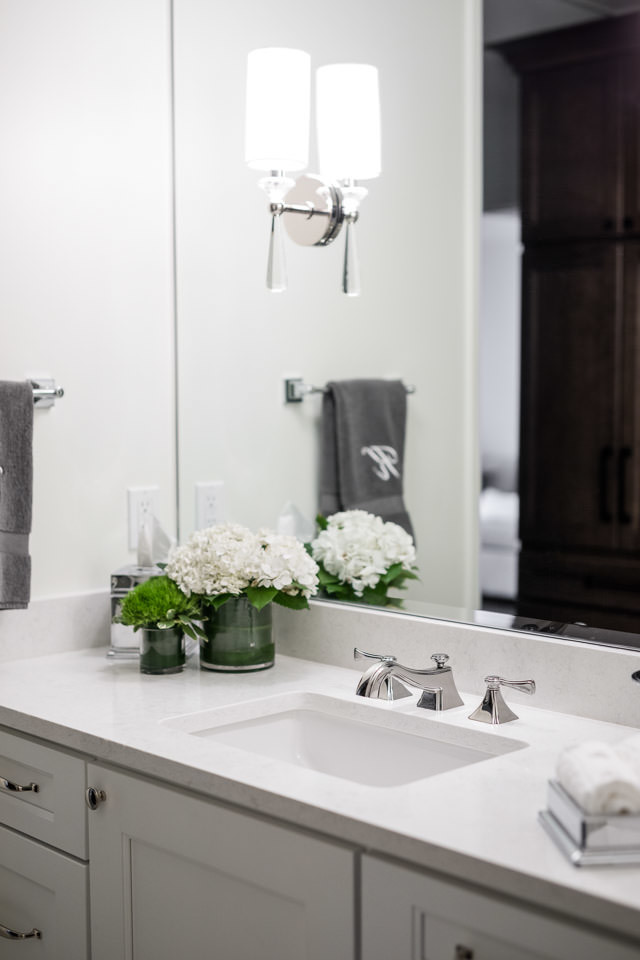 This guest bathroom vanity and entrance doubles as the main powder room for the home. Stalburg Design created a visual separation for this space from the rest of the bathroom, with a large custom wood