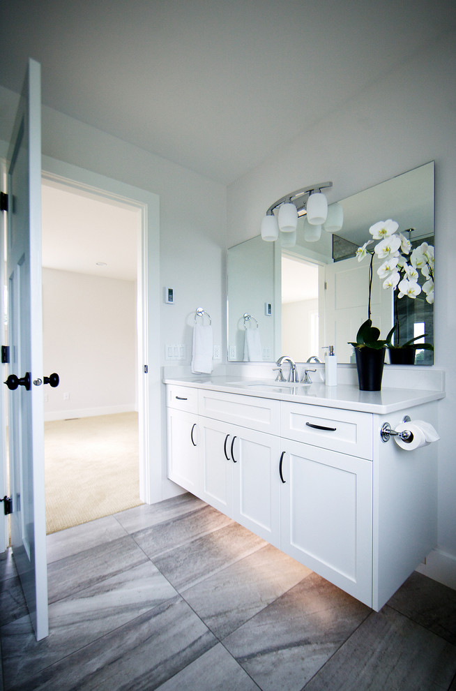 Mid-sized elegant master gray tile and ceramic tile ceramic tile doorless shower photo in Vancouver with an undermount sink, shaker cabinets, white cabinets, quartz countertops, a two-piece toilet and white walls