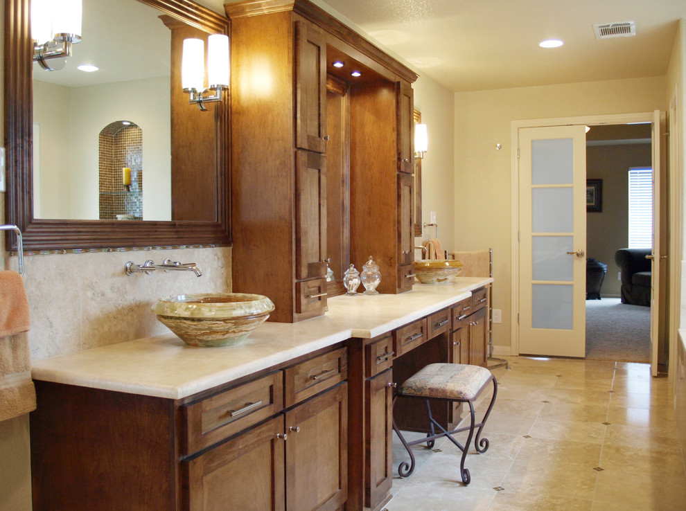 Large trendy master multicolored tile and travertine tile travertine floor drop-in bathtub photo in Austin with a vessel sink, shaker cabinets, beige walls, medium tone wood cabinets and limestone countertops