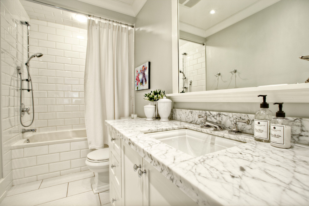 Elegant white tile and subway tile bathroom photo in Calgary with an undermount sink, shaker cabinets and white cabinets