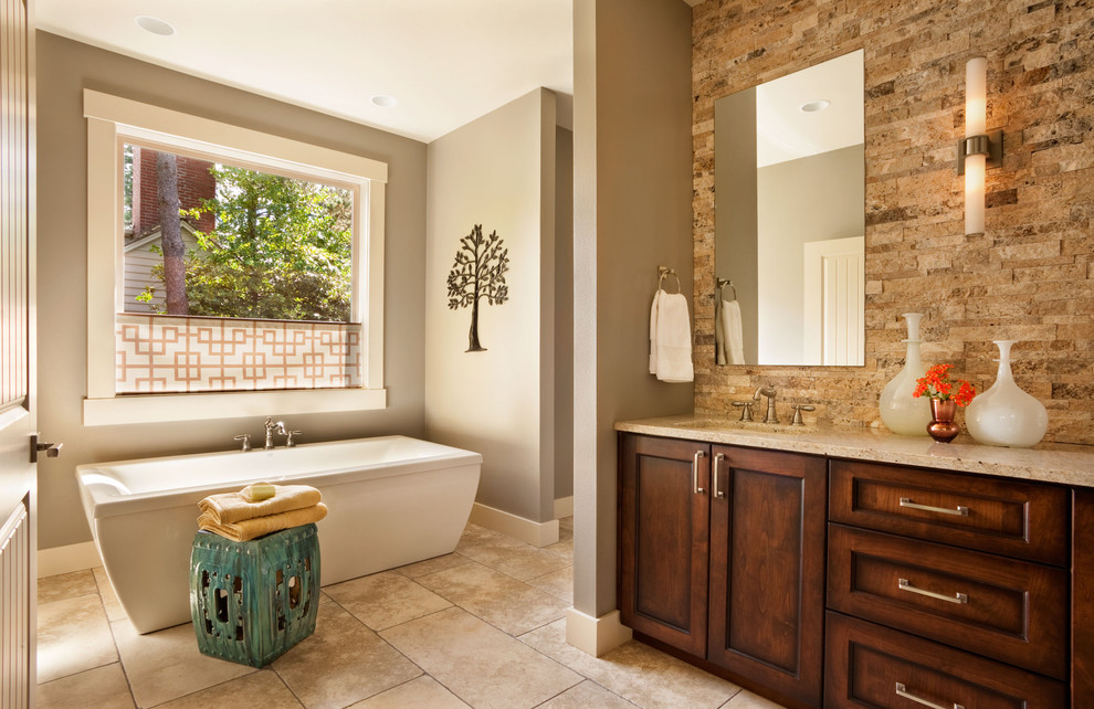 Transitional stone tile freestanding bathtub photo in Portland with an undermount sink, shaker cabinets and dark wood cabinets