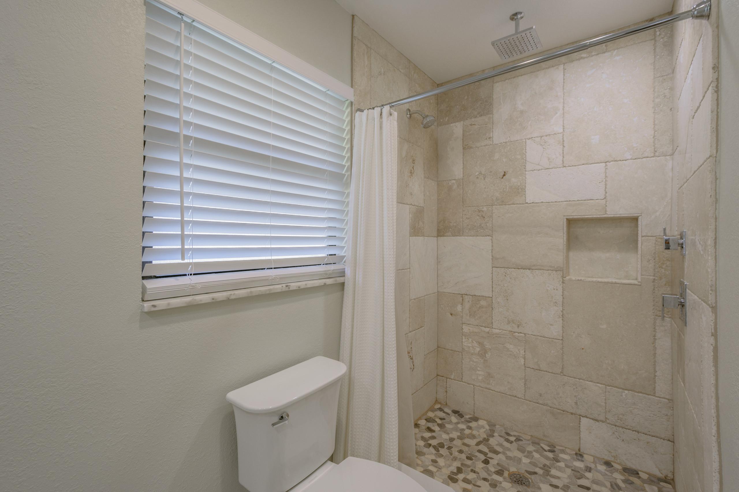 Travertine shower with custom stone shower floor