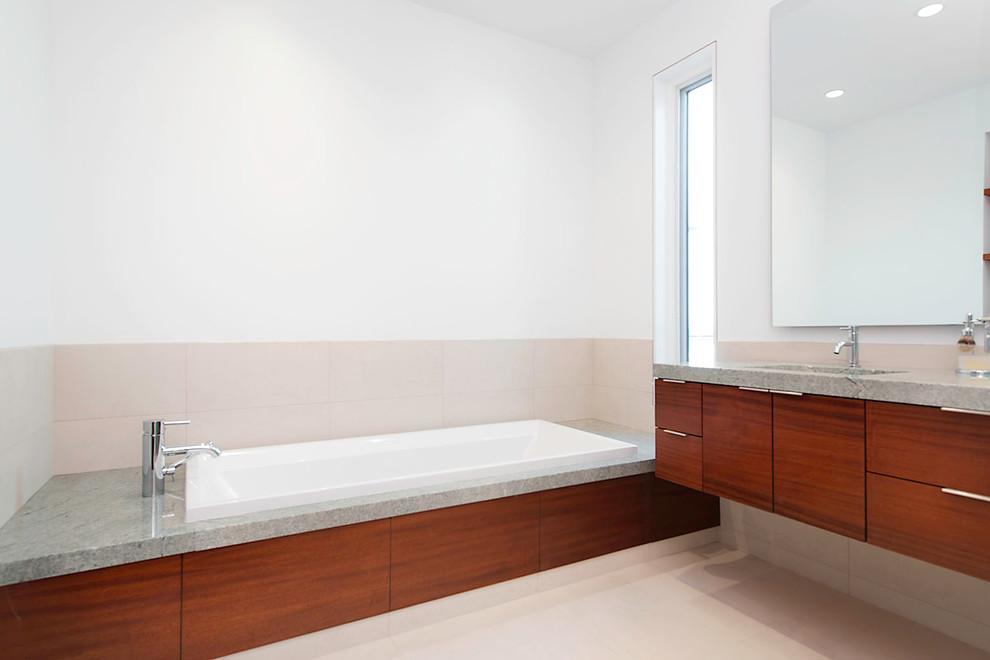 Ispirazione per una stanza da bagno padronale contemporanea di medie dimensioni con ante lisce, ante in legno bruno, vasca da incasso, piastrelle beige, piastrelle in gres porcellanato, pareti bianche, pavimento con piastrelle in ceramica, lavabo sottopiano, top in cemento e pavimento beige
