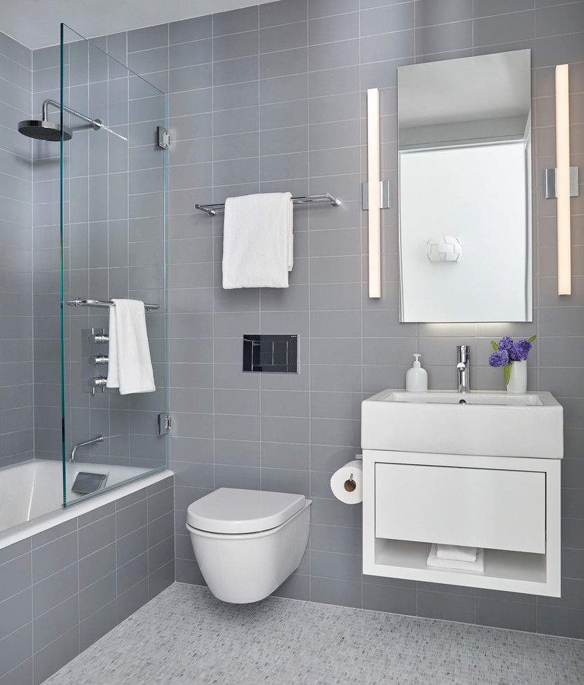 Example of a mid-sized trendy master gray tile and porcelain tile mosaic tile floor and gray floor bathroom design in New York with flat-panel cabinets, white cabinets, a wall-mount toilet, gray walls, a vessel sink and a hinged shower door