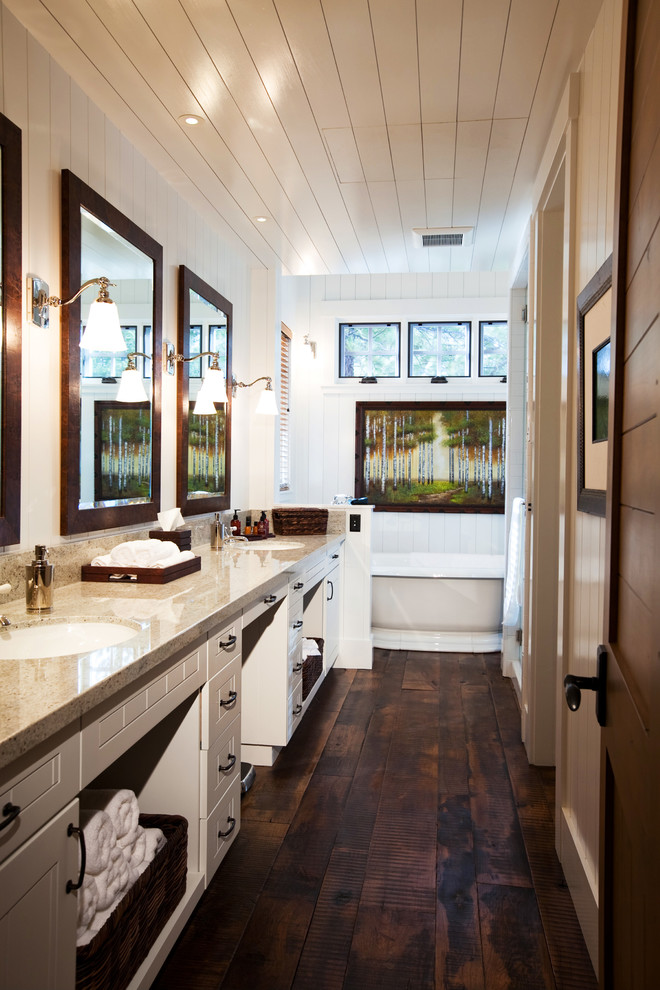Freestanding bathtub - rustic dark wood floor freestanding bathtub idea in San Francisco with an undermount sink, white cabinets and recessed-panel cabinets